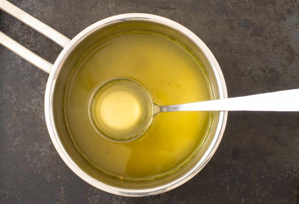Broth in a steel pot on the stove mixed with butter for basting turkey thanksgiving recipe